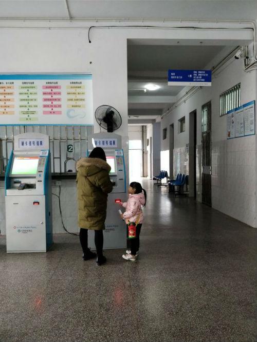 三门县中医院内一对母子在自助挂号  摄影  吴小飞