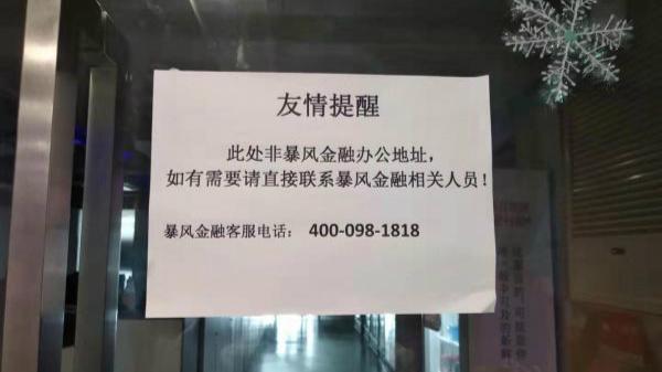 图3:在暴风集团总部的玻璃大门上贴着告示,所附暴风金融的客服电话,记者多次拨打未能接通 (丁志涛 摄)