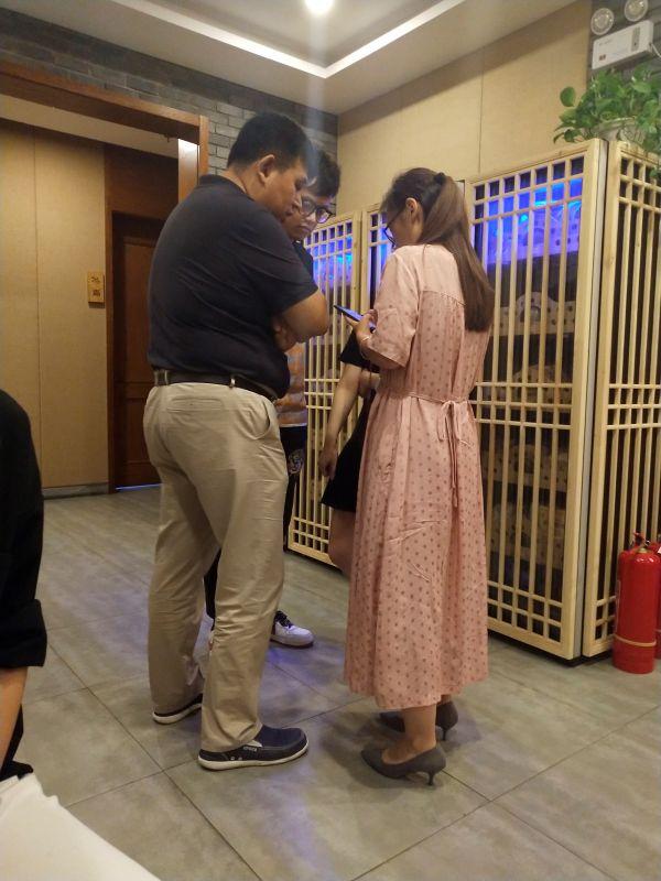 图10:史化宇与随行员工和律师在包间外低声讨论(钱玉娟 摄)
