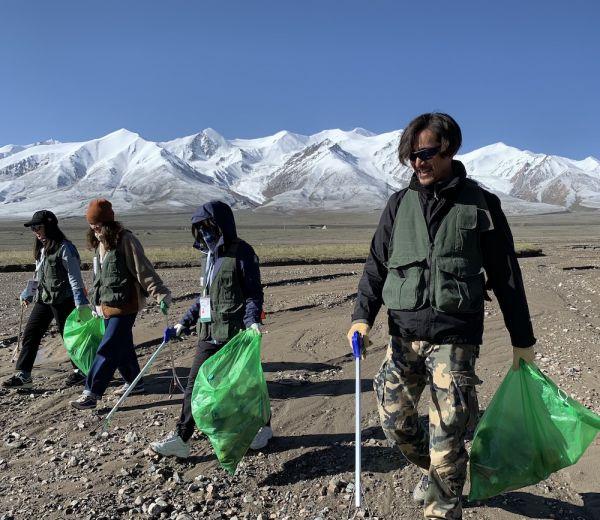 图9,(2019年7月,娱乐明星胡歌在玉珠峰下、青藏公路旁,参与捡垃圾活动。图片来源:同行的志愿者提供)