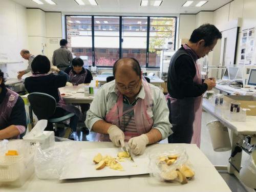 图为福岛县事恋人员检测苹果中放射性物质 王雅洁 摄