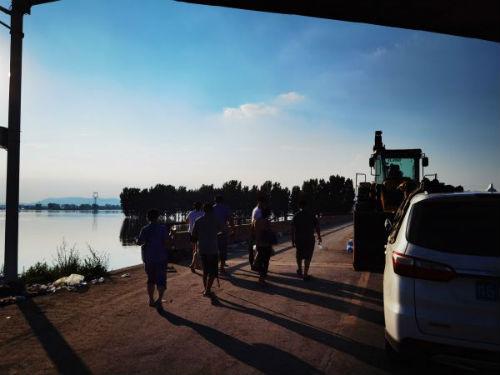 图2、7月26日下午,卫辉受灾群众跨过卫河大桥从外转移